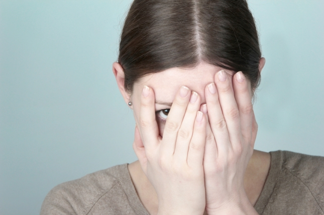 Photo of woman hiding behind her hands