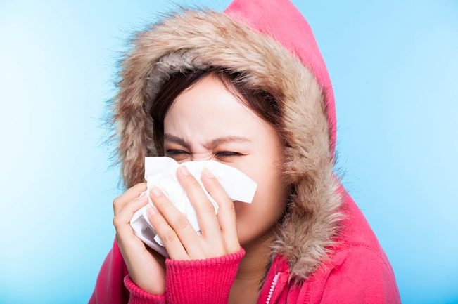 young Woman catch a cold and sneezing nose with a sweater. isola